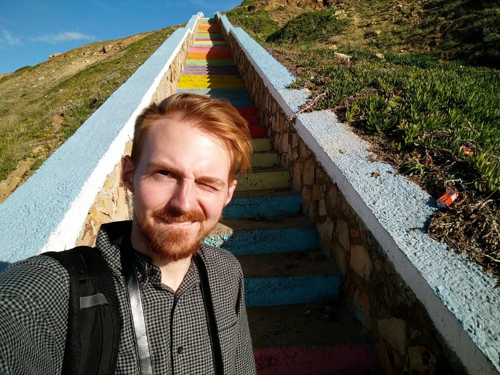 Selfie in front of some rainbow stairs leading up from a beach in Morocco.