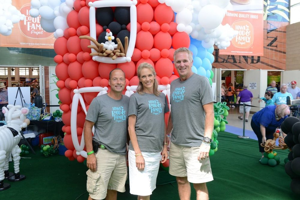 Aaron Putze, Dr. Amy Michelle Willcockson and Chuck Long volunteer at the 2017 Iowa Food & Family Project booth at the Iowa State Fair.