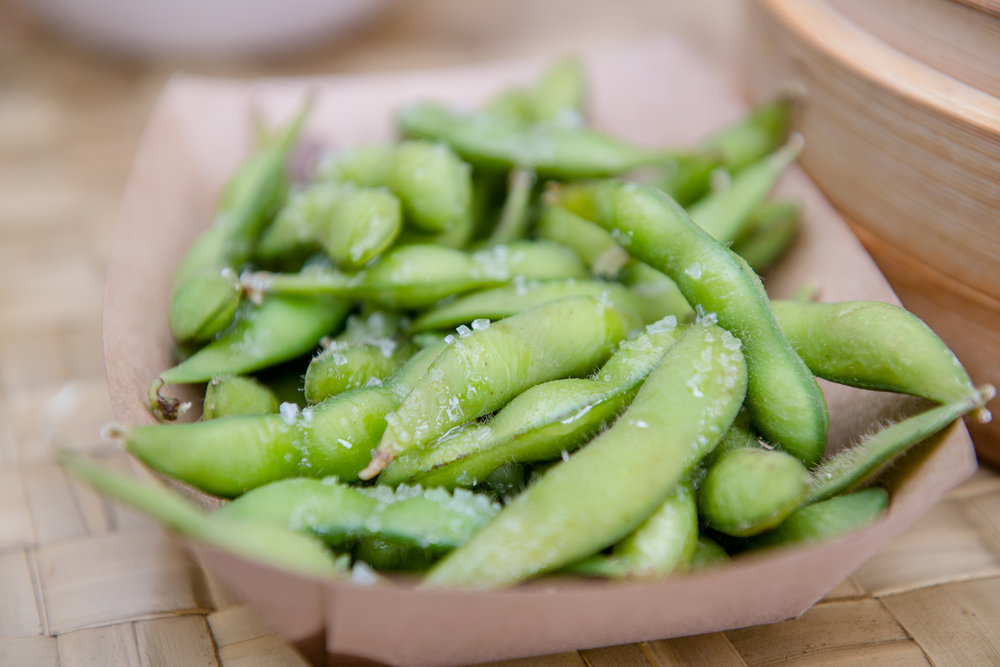 Edamame   are   soybeans that are harvested while green. At the grocery store, they are available shelled or in the pod.