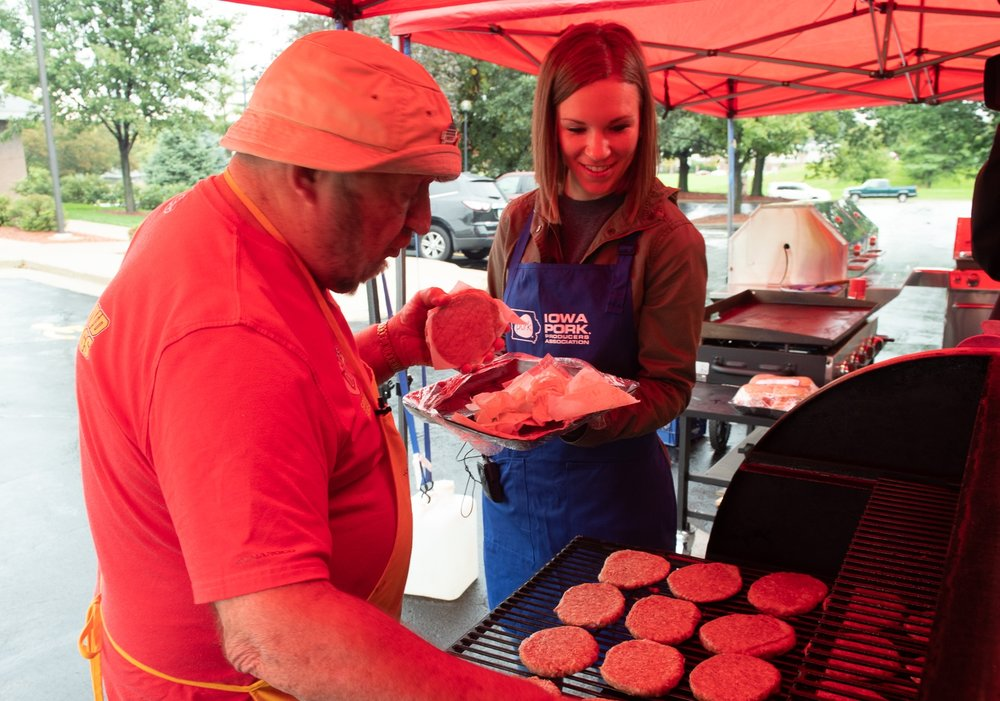Kelsey Byrnes, consumer outreach director for Iowa Pork, and Speed Herrig grill Cookies BBQ pork patties from the Hy-Vee meat counter. Photo credit: Joseph L. Murphy/Iowa Soybean Association