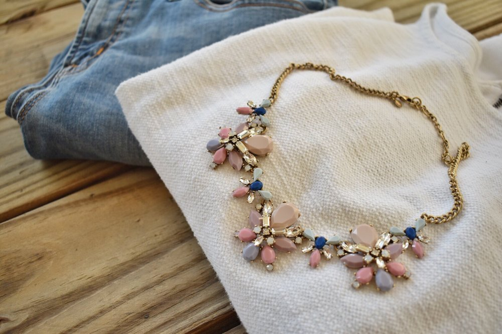 A multi-colored J.Crew brand statement necklace with a pair of blue jeans and a white t-shirt.