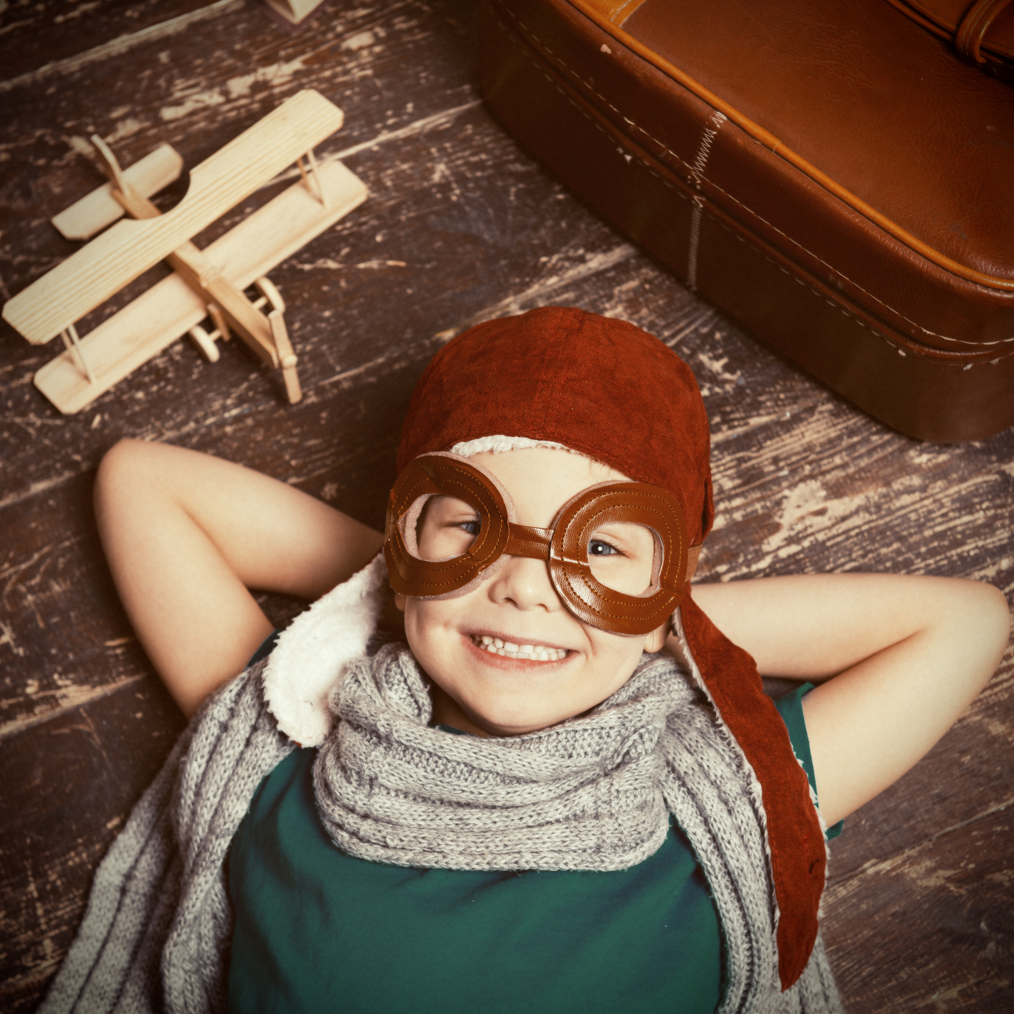 Happy little dreamer.Top view of happy little boy in pilot headwear and eyeglasses lying on the hardwood floor and smiling while wooden planer and briefcase laying near him