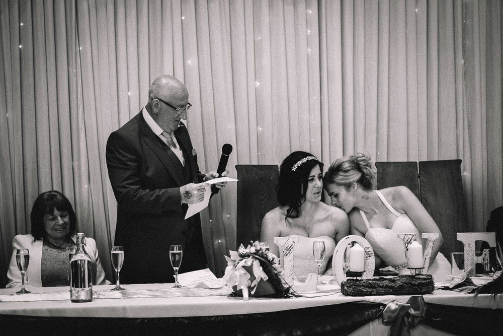 Tender moment of bride kissing during Father of the Bride speech at a relaxed same-sex wedding in Caerphilly Castle South Wales