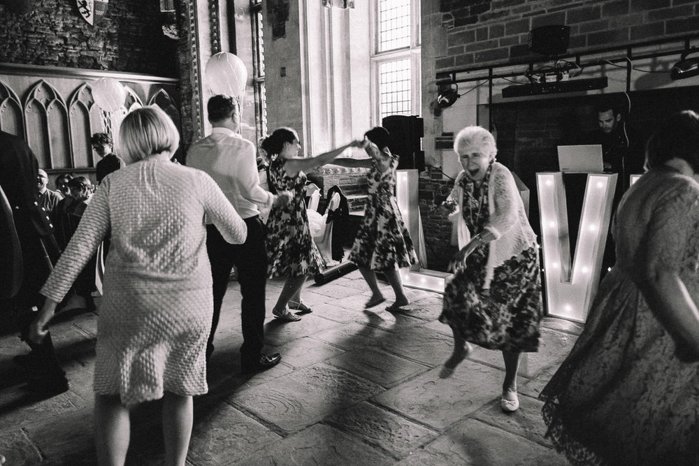 Fun candid photo of old lady on the dancefloor at an alternative wedding at Caerphilly Castle Wedding South Wales