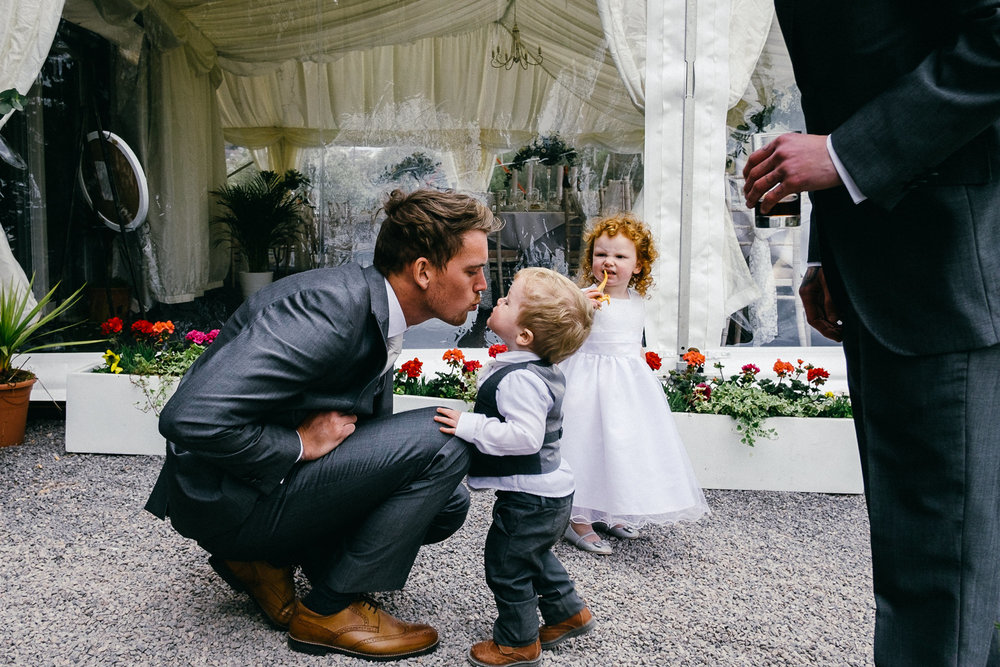 Funny natural moment of groom and son with flowergirl making faces at a relaxed wedding at Lakeside Venue Bridgend