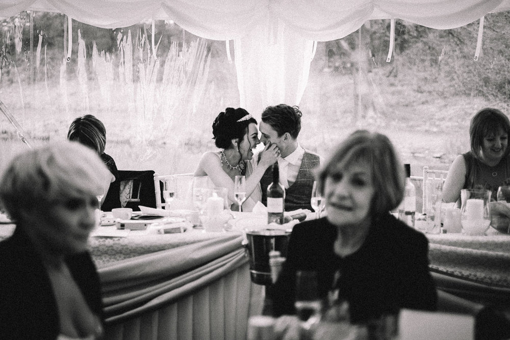 Candid wedding photograph of natural moment between bride and groom at relaxed wedding Lakeside Venue Bridgend