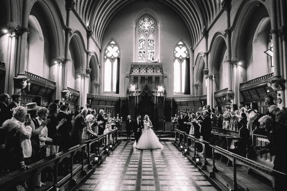 Classic black and white photo of newlyweds walking down the aisle after wedding ceremony at Stanbrook Abbey Hotel Worcester