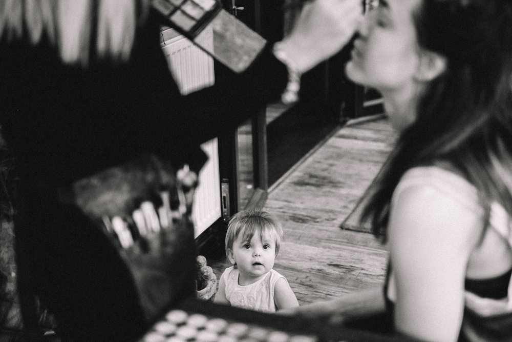 Candid photo of little girl seeing the bride getting makeup applied during bridal prep at a wedding in Newport South Wales
