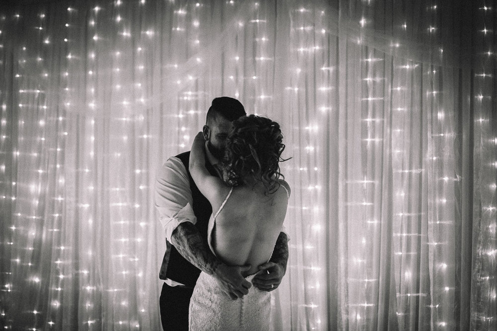 Natural black and white photograph of beautiful first dance between the bride and groom on the dancefloor of a wedding reception at Celtic Manor Golf Resort