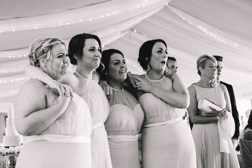 Discreet photo of bridesmaids getting emotional watching the first dance at a wedding reception in Celtic Manor Newport