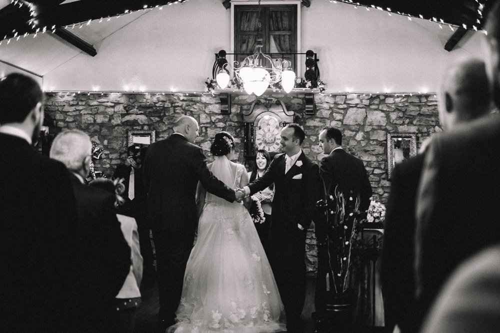 Candid black and white photograph of groom and father of the bride shaking hands at a wedding at St Mary's Golf Club in Pencoed, Bridgend by a Cardiff Wedding Photographer