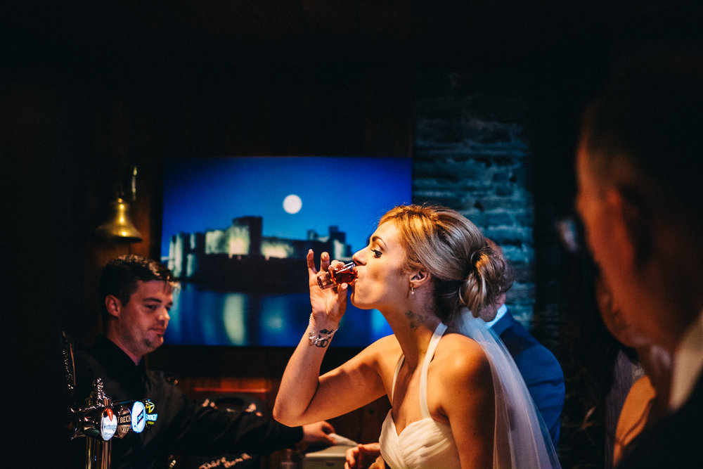 Bride doing shots - alternative fun wedding photography at Caerphilly Castle South Wales
