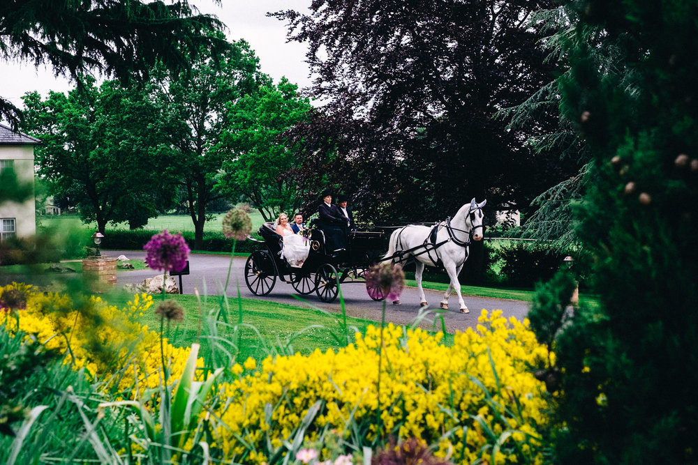 Bride and groom arriving by horse and carriage at a beautiful wedding in Stanbrook Abbey Hotel Worcester