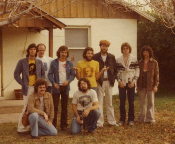 Jam session at Warren Jones' and Mark Lyons' house by the train tracks west of ASU in Tempe. Back row L to R: Zeke Gutierrez (guitar), Keith Miles (drums), Ted Goddard (guitar), Bob Fernandez (percussion), Jon Lane (bass), Joe Woznicki (guitar), Mike Hoenig (trombone); kneeling: Stan Sorensen (guitar), Warren Jones (bass). Photo by Allan Chase.