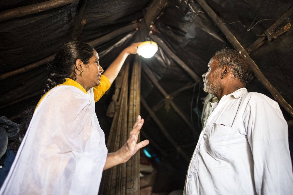 Amreen, and experienced 'Pollinator' showing a solar light to a customer in an informal settlement in Bangalore, India.