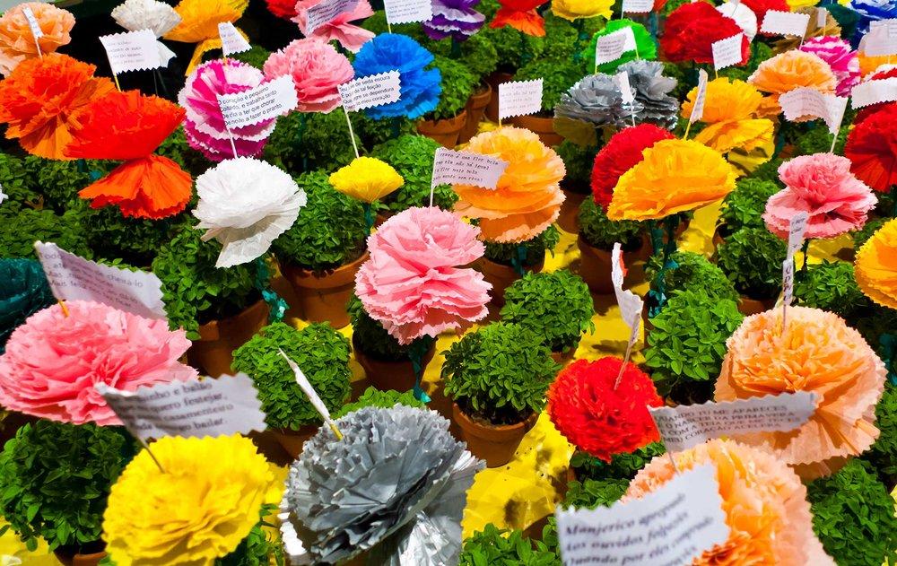 Manjericos com flores de papel coloridas e quadras populares.