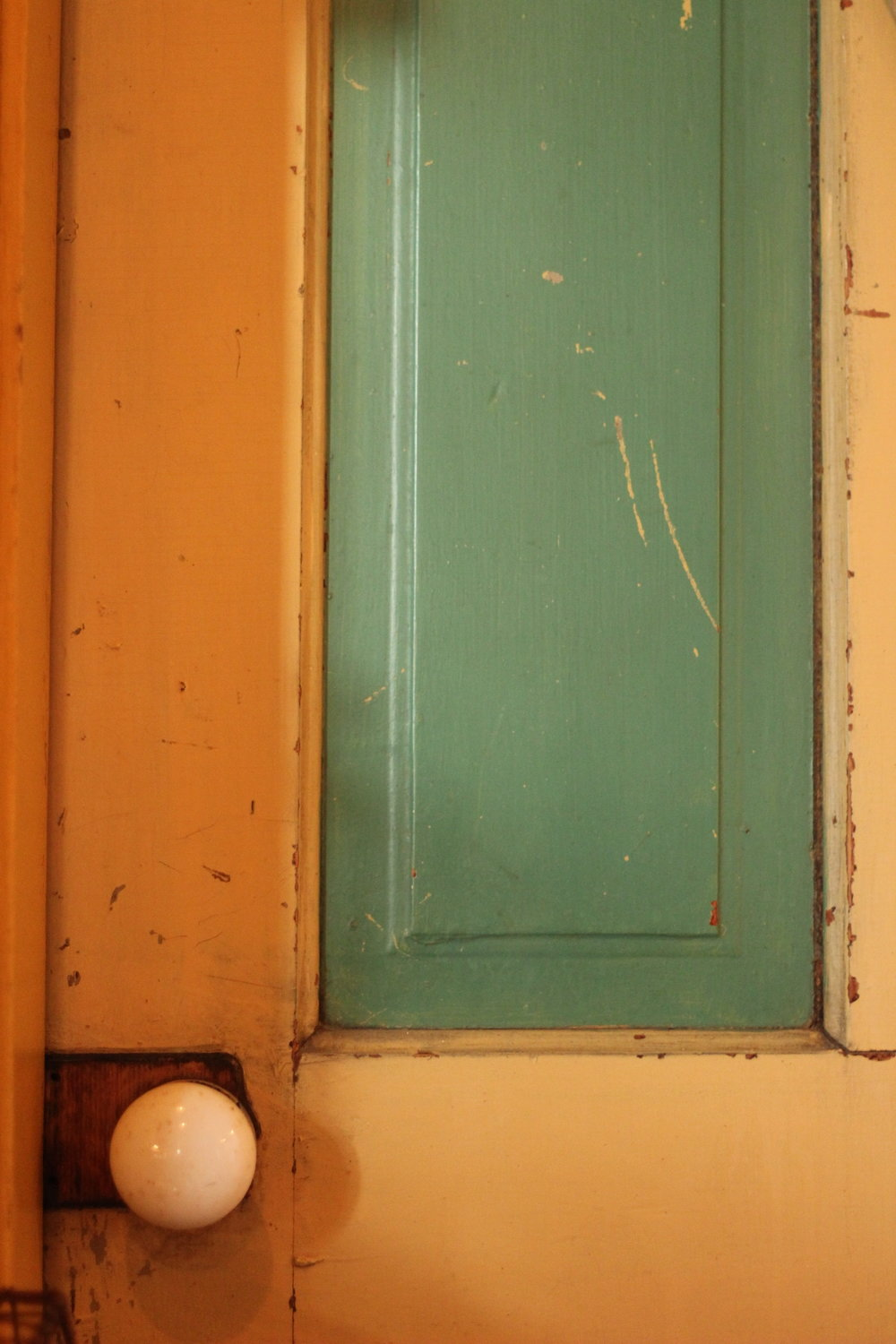 This door divides our kitchen from the front rooms of the house. It's closed and sealed until restoration of the three front rooms is complete.   It's not original to the house. The only doors here when I bought it, in 1986, were hollow core luan. One of my first tasks was to replace every door with on that is historically correct.  When we first saw this door, leaning up in an antique mall booth, we had to have it. Not only are the color spectacular, the yellow nearly matches the kitchen trim.  There are a couple of things to notice here. Humidity plays a huge role in how wood acts, how it can be put together and how finishes look and act. In a door like this the green wooden panels float between rails and stiles. They are allowed to float so that they don't split when the humidity drops -- and wood shrinks -- in the winter. The bare wood reveal around the perimeter of the panels might indicate that the door was originally painted in fairly humid conditions when the panels had expanded to full width. In the winter -- when the furnace kicks on -- household humidity plummets and wood contracts. In this case leaving bare wood around the panels.  The bumps and dings on the door are constant with doors in service areas of the house -- kitchen, pantry, basement or a back door. Many of these dings might have occurred as folks pushed open the door and dragged tools, boxes or other large items across it. My back door has similar marks from my backpack. My mother complained about my trombone case and doors over 40 years ago.