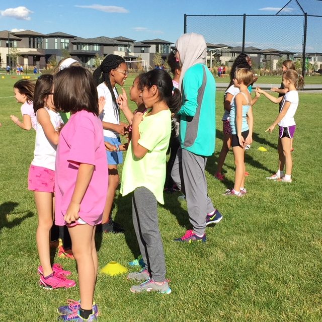 Girls on the Run building connections with their teammates during a workout at practice. Cover image: High Tech Elementary Girls on the Run participants about to cross the finish line in their 2017 5k. PC: Lisa Ordway, Girls on the Run and Bri Miller.