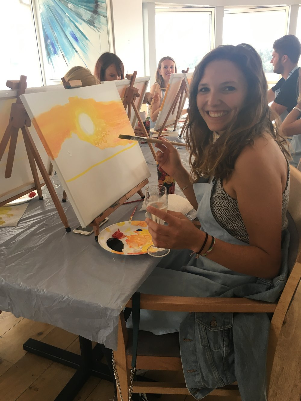 Smiling while painting a canvas