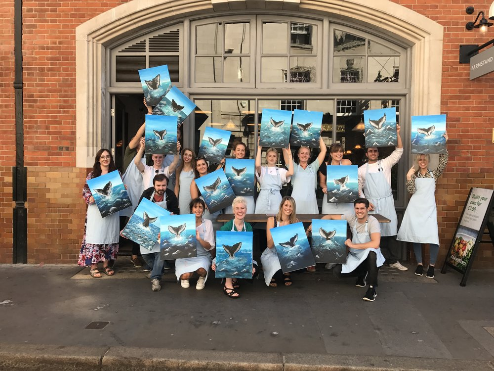 Group photo of all the whale paintings created by the class.