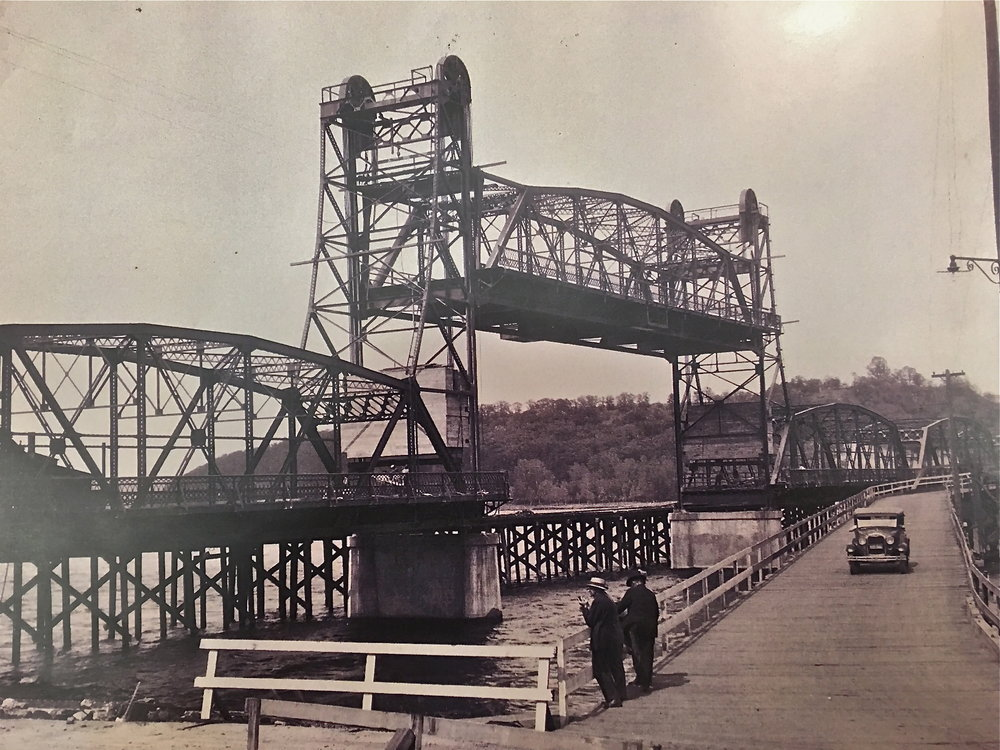 "Lift Bridge Under Construction While Pontoon Bridge Was In Use.  The Year was 1931.  Photo credit, Mr. John Runk, courtesy of the Stillwater Public Library. To travel through the ""Time Tunnel"" from 1875 to 1931, Click or Tap the photo above. Imagine yourself walking across the old wooden bridge onto the new lift bridge from 1875 to 1931 !"