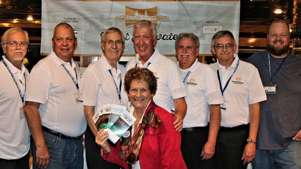 Lens Flare Stillwater Volunteers, left to Right, Gary Bressler, John Buettner, Bill Fredell, Bob Molenda, Dick Marlow, Tom Wieland, John Moore.  In front is Miriam Simmons from the St. Croix Valley Foundation.  The event is the 125th Anniversary of the Greater Stillwater Chamber of Commerce, September, 2016. Mark Luebker, who lives in South Dakota is not in the photo.