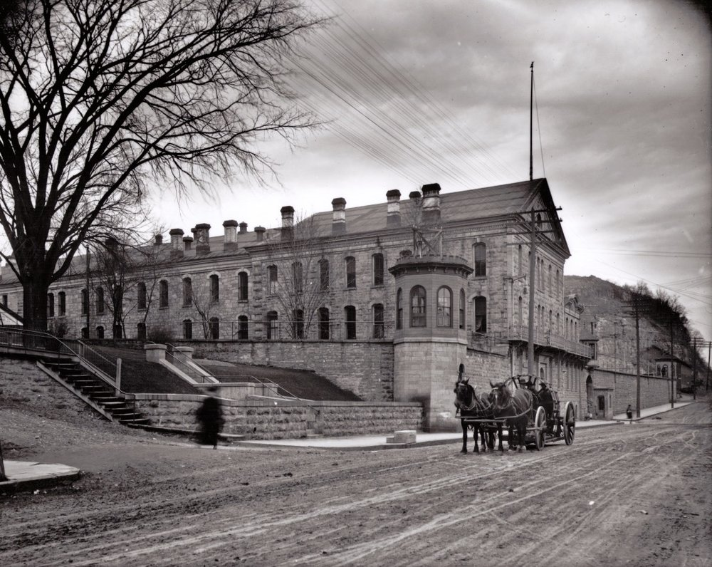 "This is a view of the Territorial Prison in 1907. The wagons are hauling two tractor wheels from the foundry. The view is looking north on Main Street. Photo credit is Mr. John Runk, courtesy of The Stillwater Public Library, John Runk Collection.   Click or Tap on the photo to view a ""Time-Tunnel"" morph of this same location going from 1907 to 2016."