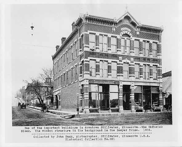The McKusick Block, located on the Northwest corner of Myrtle and Main Streets. This photo was taken in 1886 and is sourced from the John Runk Collection, courtesy of the Stillwater Public Library. In the background you are able to see the Sawyer House. The streets were dirt at that time.       Narrative    by Robert Molenda   The McKusick Building was built in 1880. You have to exercise your history detective skills in order to see the ghost of the old building hidden in the building today. Presently, it is a two story building that has a marble facing. It covers the masonry brick frontage of the old building, but with a little effort, you can see the ghost of the old building that originally stood at this location.    To Read More About The McKusick Building, Click or Tap on the Highlighted Text.