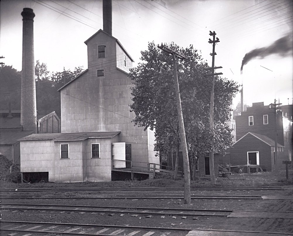 This is the Commander Elevator in 1917. Photo credit is Mr. John Runk, courtesy of the Stillwater Public Library. To the left of the elevator is the smokestack from the power generator for the area.  To view this same location in 1975, Click or Tap the photo above.