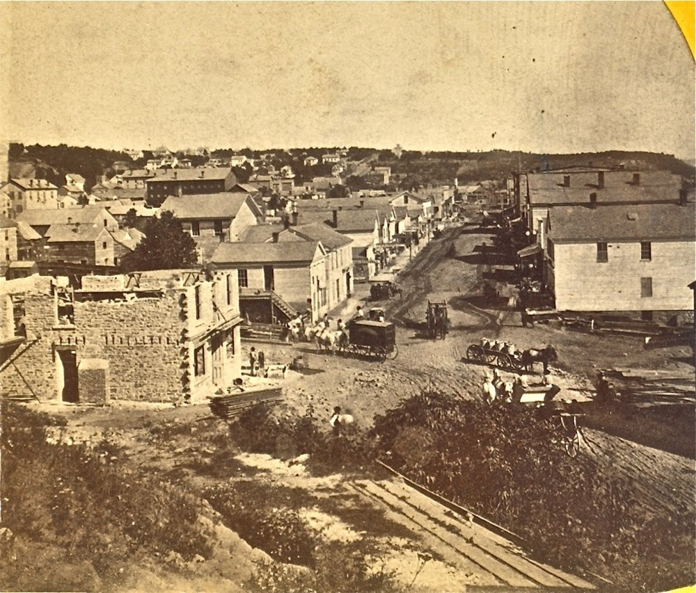 This is a later view than the previous photo, showing the construction of the brick building on the corner of Nelson and Main Streets. This photo may have been taken from the hillside or the building that stood at this location. The photo is from the John Runk Collection, courtesy of the Stillwater Public Library.