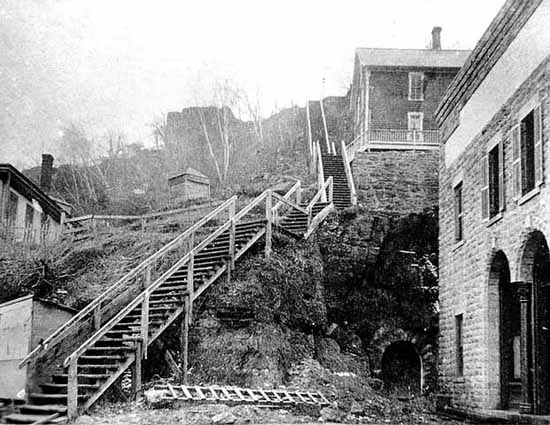 This view up the stairs does after the construction of the brick building in the foreground. The stairs are still wooden. This photo is from the John Runk Collection, courtesy of the Stillwater Public Library.