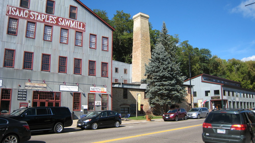 This is the same location of the Staples Sawmill in 2017. The photo shows the large steel clad building to the left of the stone powerhouse and chimney. This was once the location of the Stillwater Manufacturing Company, a subsidiary of The Northwest Thresher Company.