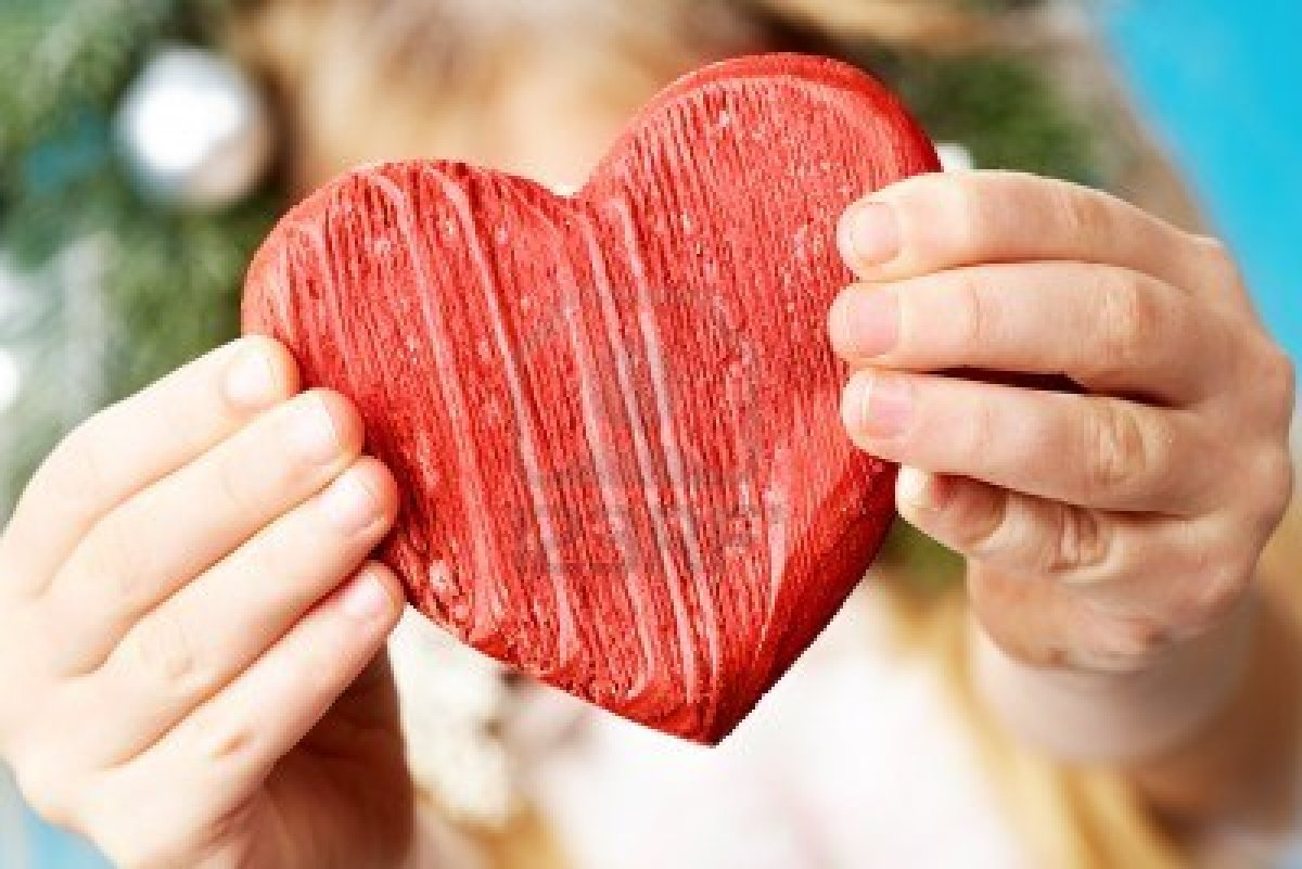 9360310-close-up-of-red-wooden-heart-in-child-s-hands-showing-it