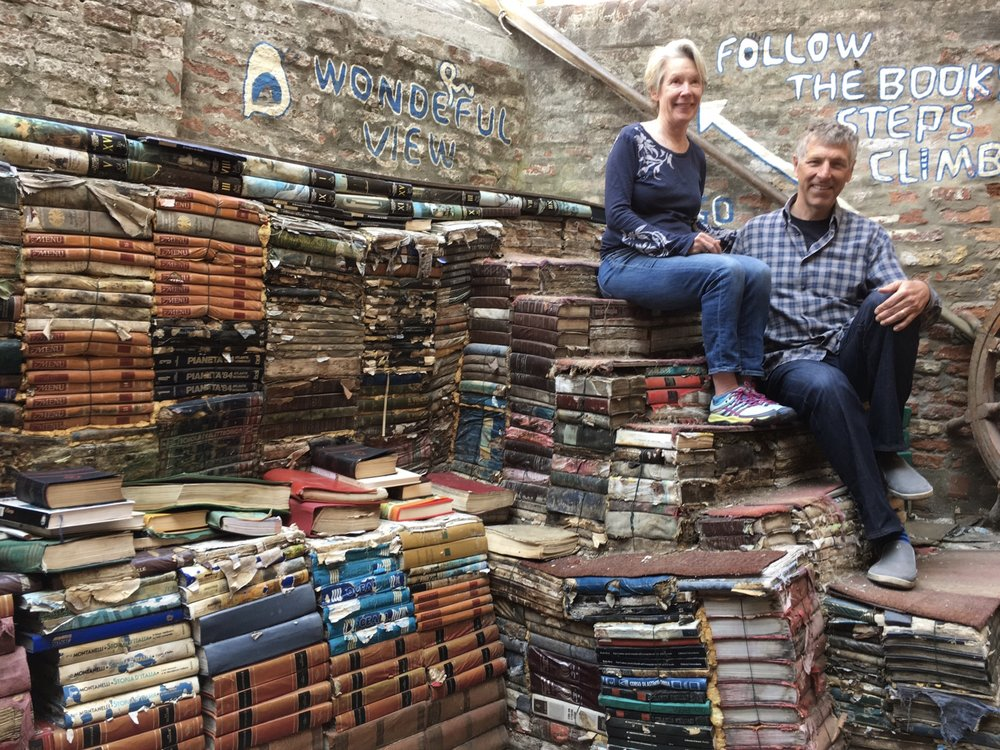 Walk up a flight of steps made of water damaged books at Acqua Alta to a canal