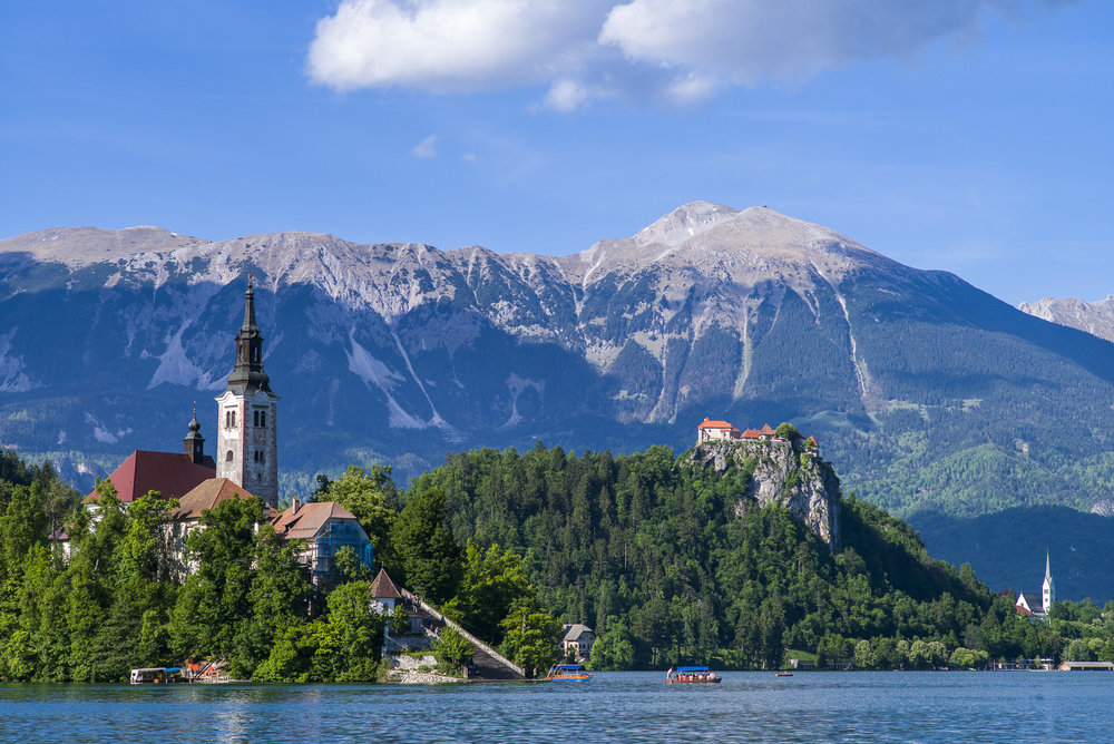 Bled Island Pilgrimage Church and Castle in the foreground and the Julian Alps in the distance