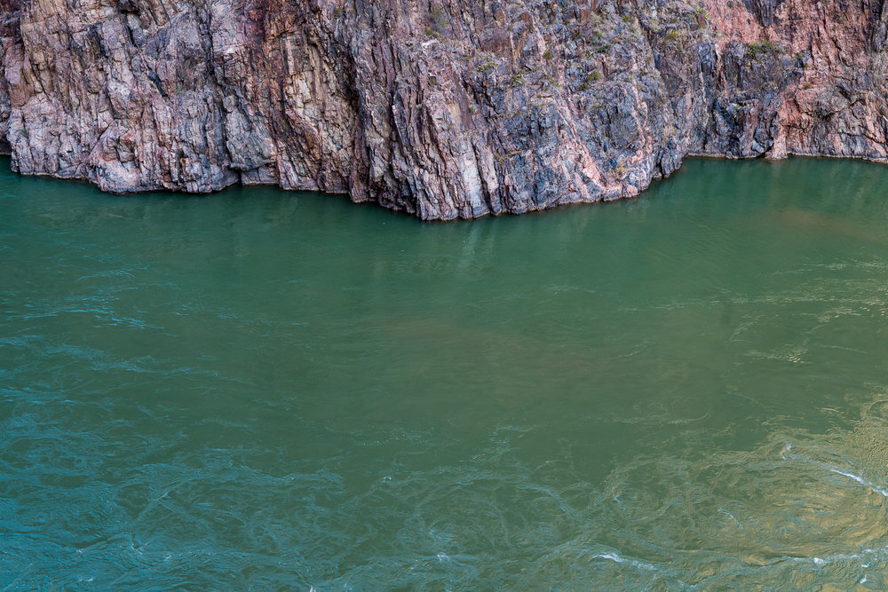 The green water of the Colorado next to the 2 billion year old rocks
