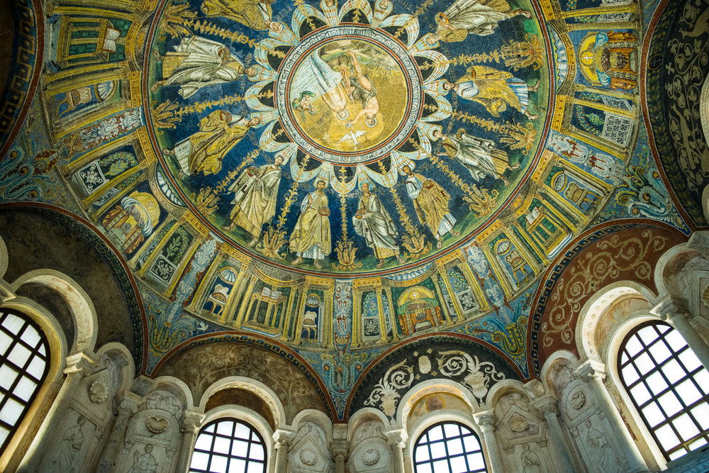 Mosaics adorning the dome ceiling of the Baptistry of Neon. Sculpted marble and arched windows supporting the dome.