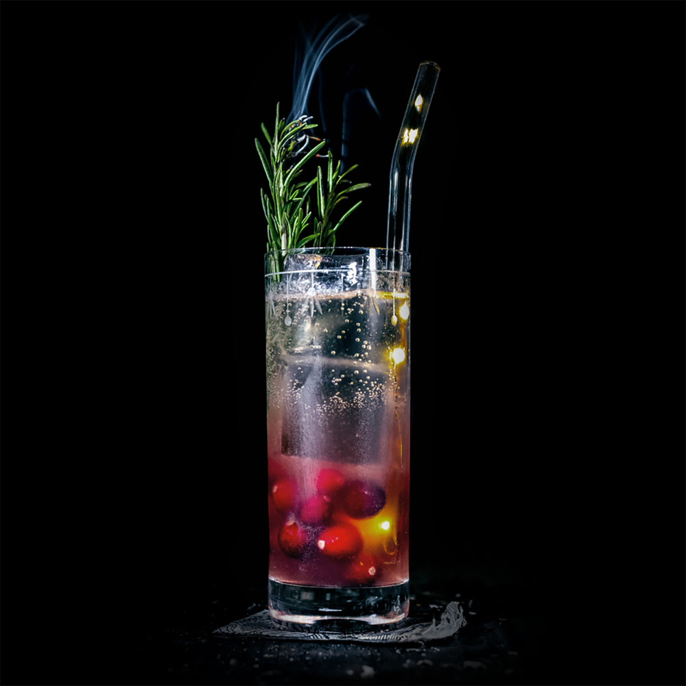 HOLIDAY IN OAXACA  INGREDIENTS  - 1.5 oz. Espadin - 1 oz. Cranberry Syrup (1 part unsweetened Cranberry Juice to 1 part sugar)  - .5 oz. Fresh Lime Juice  METHOD  Shake and strain into a collins glass. Top off with soda water and garnish with a rosemary sprig.