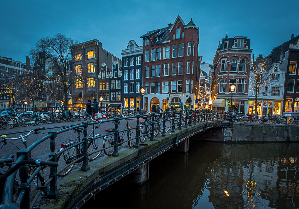 ©Ayash Basu. The bicycles and the railing are used as leading lines to guide the viewer to the main subject of the images – the canal houses in the background as they light up in the evening in Amsterdam.