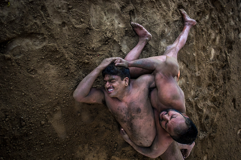 © Ayash Basu. Traditional Indian wrestlers in the middle of a bout in Kolkata. A straight on photo at eye level would have been a standard shot but I took this from a height for two reasons – to get more of the wrestler's body in the frame as opposed to just their faces or hands, and to simplify the composition by avoiding trees, buildings and other people in the background which would distract from the main subject.