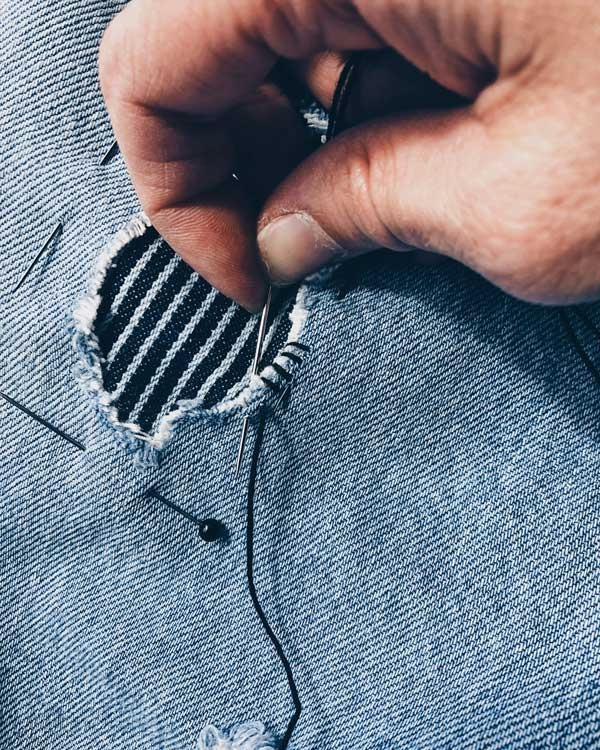 6. Whip (stitch) it! - Start by running a whip stitch around the edge of the hole, make sure you catch the patch (stripe fabric) as you go. This secures the raw edge of the garment, as well as being the first step in attaching the patch.