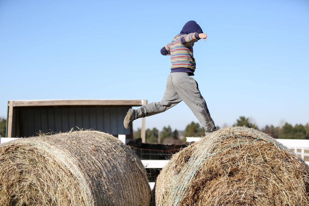 My oldest son jumping on the hay bales on the coldest day of the weather. That's ice, not water, on his pants.