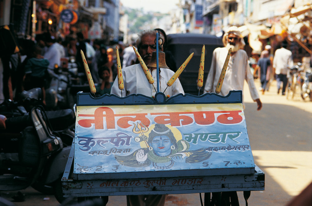 "A vendor selling milk ice-cream. The text reads 'Blue Throat. Milk ice-cream depot; cashew pistacio, filled with almonds; 2, 3, 5, 7 rupees.' ""Blue Throat"" is another name for Lord Shiva who turned blue because he consumed lethal poison, symbolised by the naga around his neck, to save the world. Photo: Ajmer, India"