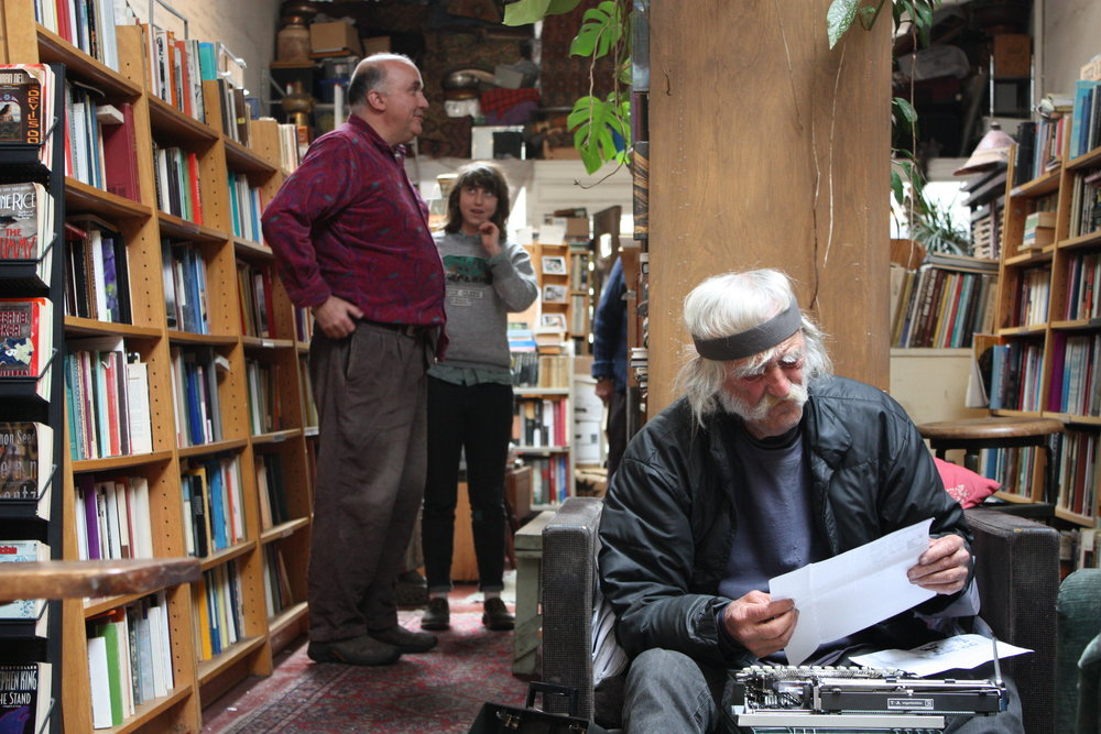 Swan (right), who can be found in or around Adobe Books most days, is typing a weekly publication that he authors and distributes in the neighborhood while McKinley (left) helps Lauren (center)locate a book.Swan can be found snoozing in one of the shops cozy chairs late mornings, and heads out to feed the neighborhood birds in the afternoon.