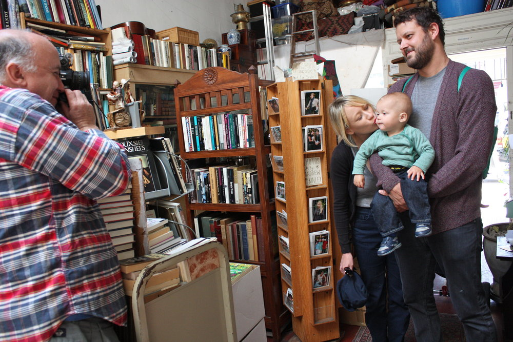 A talented portrait photographer, McKinley snaps a family photo of 14-month-old Weston Arthur, son of Katherine Rosch and Brion Nuda Rosch who stopped in to say hello. McKinley shoots about ten rolls of 35mm film per month, mainly of friends and people he knows. His photographs are on display in the store for people to browse, but they are not for sale.
