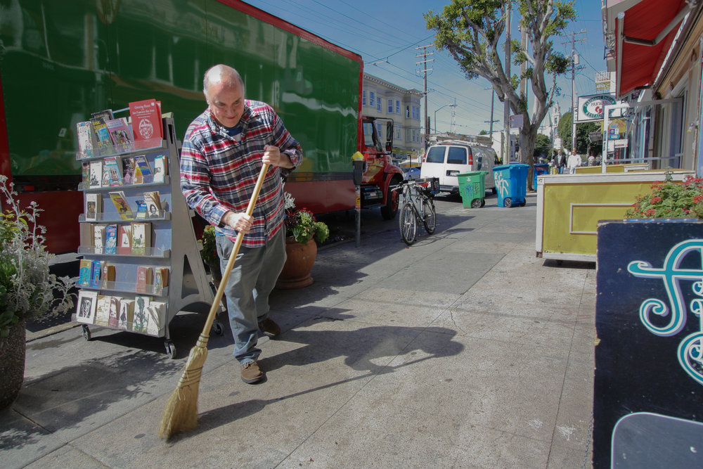 Starting the day, shop owner Andrew McKinley sweeps in front of Adobe after rolling out the sidewalk book display.