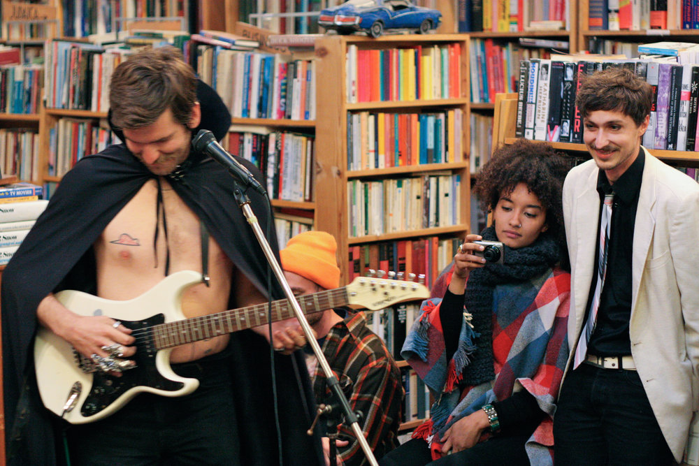 Grant LaValley (left) plays guitar for an intimate gathering of friends and customers including Charis Briley (center) and Dan Olsen (right) on a Friday evening in the bookstore. McKinley is a strong supporter of the arts and has a backroom gallery where local artists can show their work.