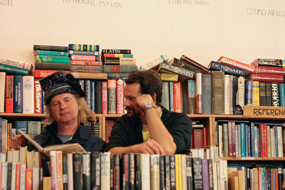 Mick Goldwater (left) and Zander Macky (right) look at a book while listening to an evening music performance at Adobe.