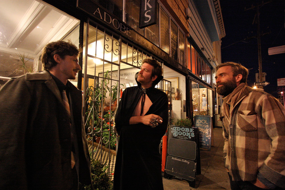 Following a performance of music, puppetry, and poetry, Dan Olsen (left), Grant LaValley (center), and Andrew Berg (right) chat outside Adobe before heading out to a goth-themed party. McKinley planned to join them.