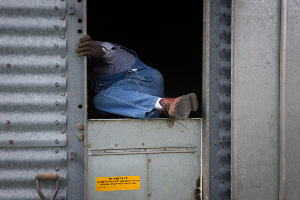 In preparation for the corn harvest, Carl climbs into the grain silo to sweep out the last of the wheat.